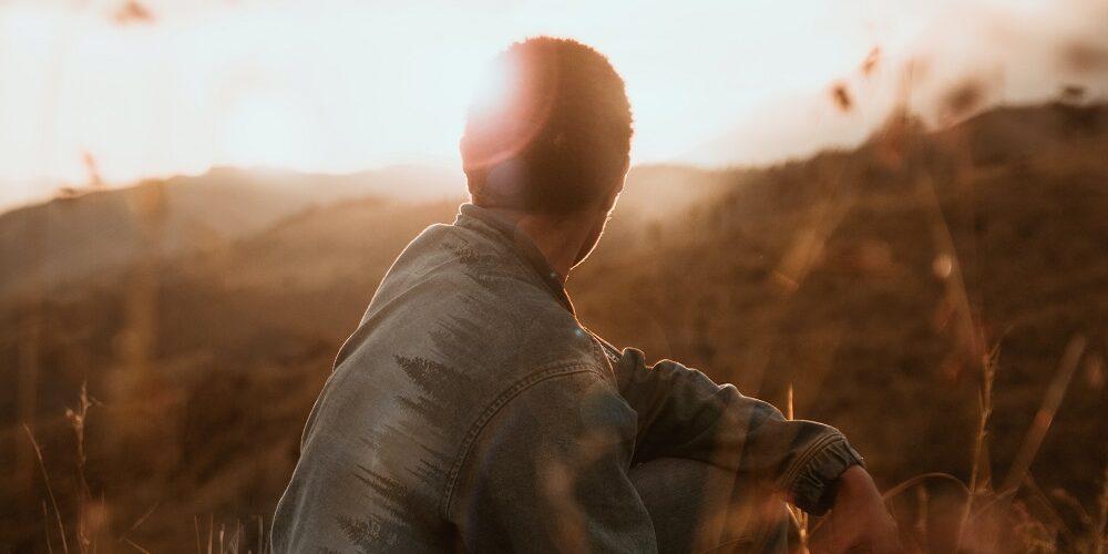 man in field looking to horizon